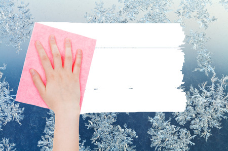 deletes: weather concept - hand deletes winter snowflake on window by pink rag from image and white empty copy space are appearing