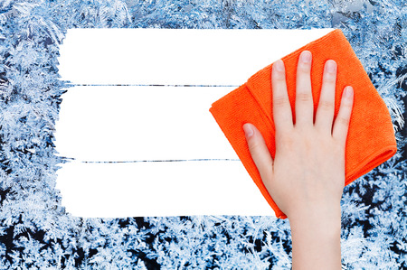 deletes: weather concept - hand deletes winter frozen texture on glass by orange rag from image and white empty copy space are appearing