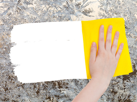 deletes: weather concept - hand deletes winter frozen pattern on glass by yellow rag from image and white empty copy space are appearing Stock Photo