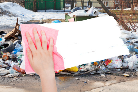 deletes: ecology concept - hand deletes urban dumpster by pink rag from image and white empty copy space are appearing Stock Photo