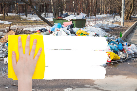 deletes: ecology concept - hand deletes outdoor trash by yellow rag from image and white empty copy space are appearing Stock Photo