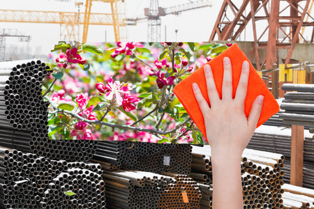 deletes: ecology concept - hand deletes industrial landscape by orange cloth from image and spring pink blossoms are appearing