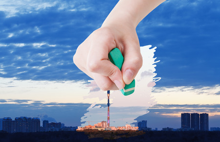 deletes: weather concept - hand deletes blue sunrise over city by rubber eraser from image and pink sunset are appearing