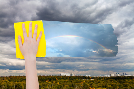 deletes: weather concept - hand deletes gray rainy clouds over city by yellow cloth from image and rainbow is appearing