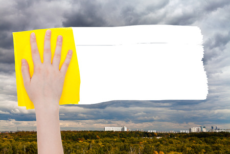 deletes: weather concept - hand deletes rainy clouds over town by yellow rag from image and white empty copy space are appearing