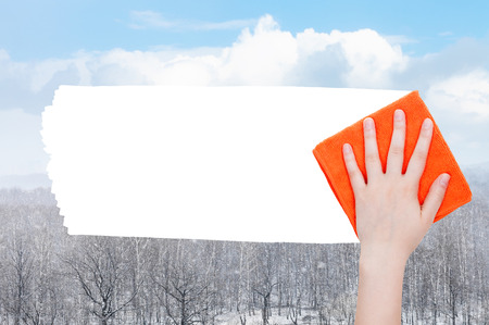deletes: weather concept - hand deletes snow over forest by orange rag from image and white empty copy space are appearing Stock Photo