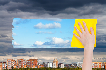 deletes: weather concept - hand deletes dark clouds over city by yellow cloth from image and blue sky with white clouds are appearing Stock Photo