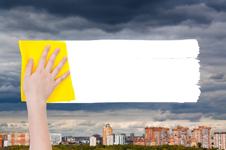 deletes: weather concept - hand deletes rainy clouds over urban houses by yellow rag from image and white empty copy space are appearing
