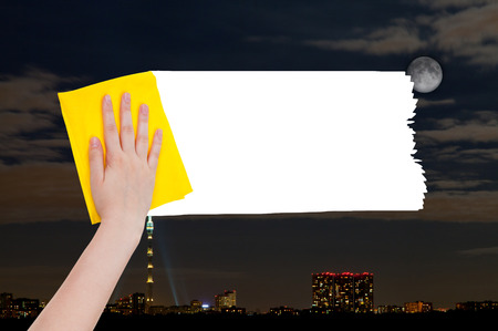 deletes: weather concept - hand deletes night city by yellow rag from image and white empty copy space are appearing Stock Photo