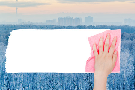 deletes: weather concept - hand deletes frozen forest by pink rag from image and white empty copy space are appearing