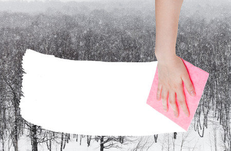 deletes: weather concept - hand deletes snow over woods by pink rag from image and white empty copy space are appearing
