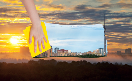 deletes: weather concept - hand deletes yellow sunrise over city by yellow cloth from image and day cityscape is appearing