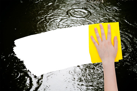deletes: weather concept - hand deletes rainy puddle by yellow rag from image and white empty copy space are appearing Stock Photo