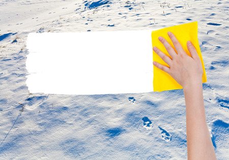 deletes: season concept - hand deletes snow surface by yellow rag from image and white empty copy space are appearing Stock Photo