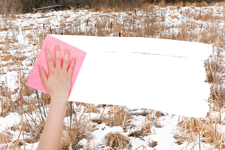 deletes: season concept - hand deletes frozen swamp by pink rag from image and white empty copy space are appearing Stock Photo