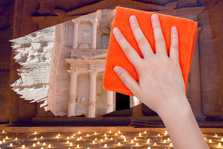 deletes: travel concept - hand deletes night view of Petra by orange rag from image and day view of ancient town Petra is appearing Stock Photo