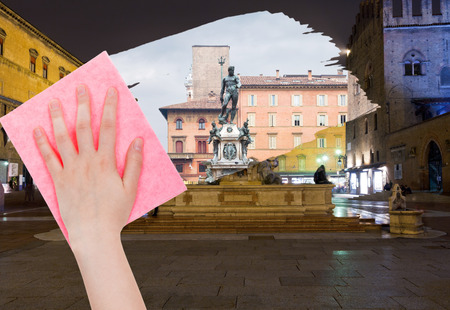 deletes: travel concept - hand deletes Bologna night cityscape by pink cloth from image and daily city view is appearing