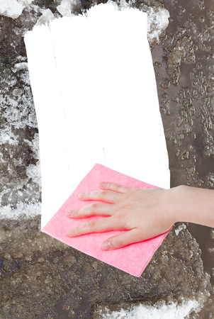 deletes: weather concept - hand deletes melting snow by pink rag from image and white empty copy space are appearing Stock Photo