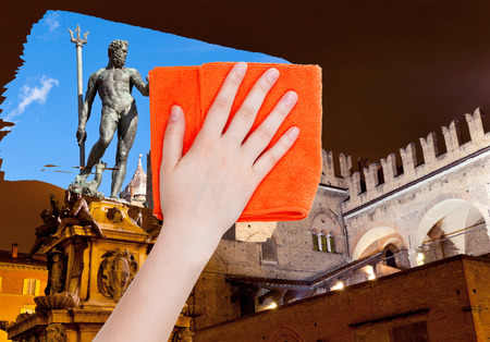 deletes: travel concept - hand deletes Bologna night scene by orange cloth from image and daily city view is appearing