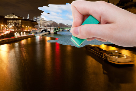 deletes: travel concept - hand deletes night scenery of Paris city by rubber eraser from image and day cityscape are appearing