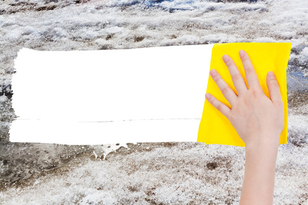 deletes: weather concept - hand deletes melting snow by yellow rag from image and white empty copy space are appearing