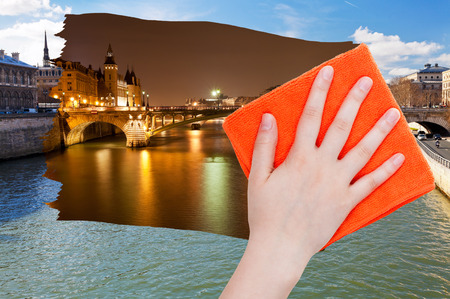 deletes: travel concept - hand deletes day view of Paris by orange cloth from image and night cityscape is appearing