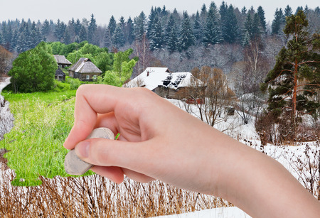 deletes: season concept - hand deletes winter village by rubber eraser from image and summer country landscape are appearing
