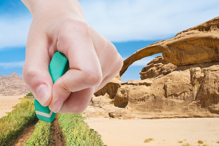 deletes: weather concept - hand deletes sand in desert by rubber eraser from image and green grass and country road are appearing