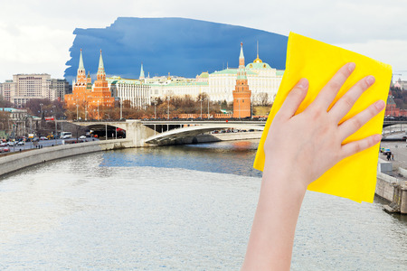 deletes: travel concept - hand deletes morning view of Moscow by yellow cloth from image and evening cityscape is appearing Stock Photo