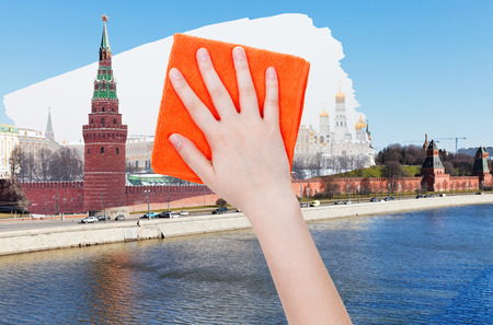 deletes: travel concept - hand deletes summer view of Moscow by orange cloth from image and winter snowing cityscape is appearing Stock Photo
