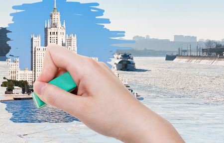 deletes: season concept - hand deletes frozen Moskva river by rubber eraser from image and Moscow summer cityscape are appearing