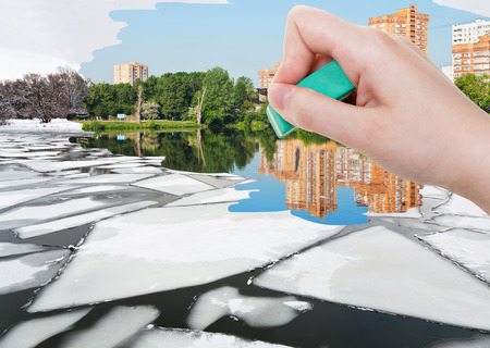 deletes: weather concept - hand deletes ice floe near river waterfront in winter by rubber eraser from image and summer cityscape are appearing