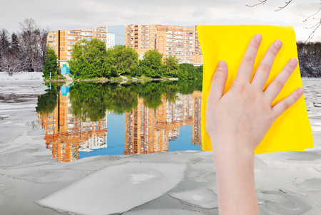 deletes: season concept - hand deletes ice block in winter river by yellow cloth from image and summer cityscape is appearing Stock Photo