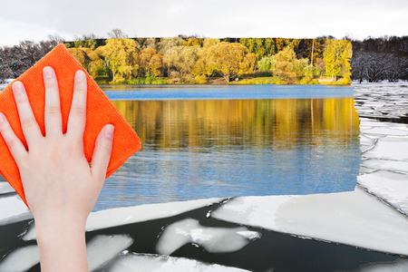 deletes: season concept - hand deletes ice floe in winter river by orange cloth from image and water and green woods are appearing Stock Photo