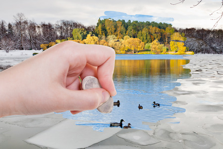 arise: weather concept - hand deletes ice blocks in winter river by rubber eraser from image and autumn natural landscape are appearing