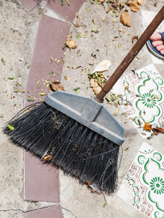 sweeps: broom sweeps leaf litter from the concrete walkway