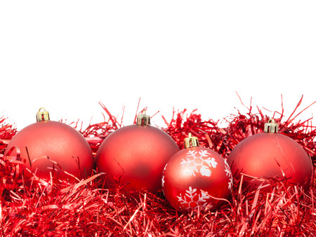 christmas decorations with white background: four red Christmas baubles and tinsel isolated on white background