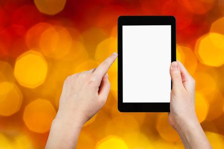 flickering: fiesta de navidad concepto - mano con Tablet PC con pantalla cortada en el fondo de color amarillo y rojo parpadeante grandes luces de Navidad de guirnaldas en el �rbol de Navidad