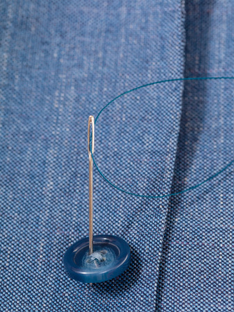 attaching: attaching of button to blue silk dress by needle close up