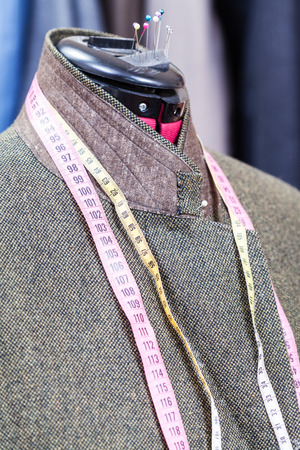 sartorial: tailoring of male woolen tweed jacket on dummy and ready suits on background