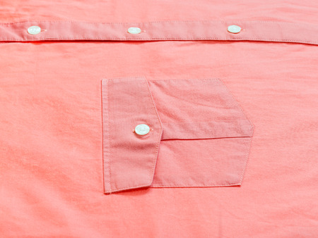 sartorial: buttoned pocket of red shirt close up
