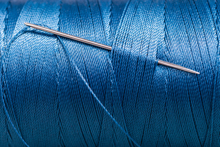 sewing needle in blue thread bobbin close up