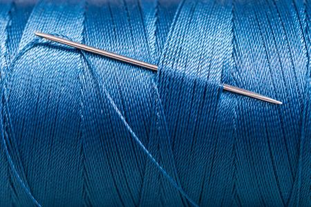 naald in blauw draad spoel close-up Stockfoto