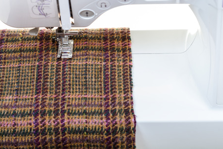 woolen cloth: foot of the sewing machine on woolen cloth close up