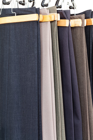 sartorial: various woolen trousers on hangers in tailoring atelier close up Stock Photo