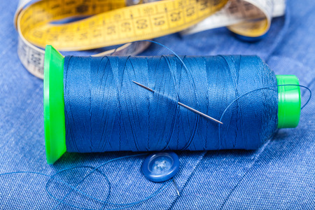 sartorial: tailoring still life - thread bobbin with needle, button, measure tape on blue silk cloth Stock Photo
