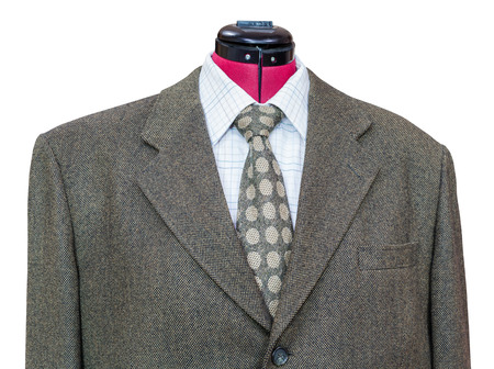 tweed: business suit on tailor mannequin - green tweed jacket with shirt and tie close up isolated on white background