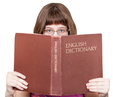 English dictionary: direct view of girl with glasses looks over English Dictionary book isolated on white background Stock Photo