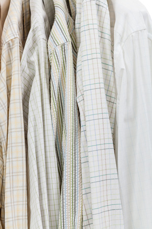 shirts on hangers: various shirts on hangers in wardrobe close up Stock Photo