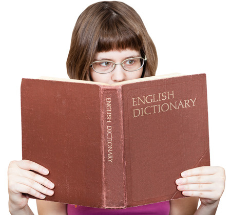 English dictionary: girl with glasses reads big English Dictionary book isolated on white background